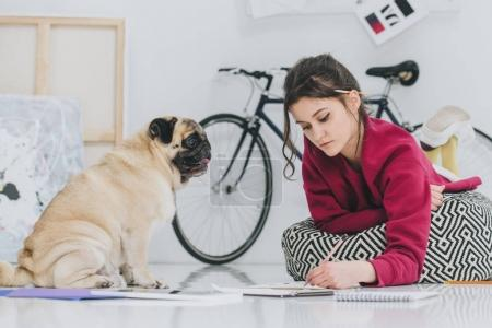 Attractive young girl drawing on floor with pug pet