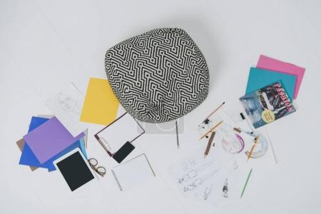 Fashion illustrations and digital devises on floor with cushion