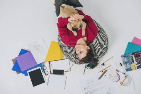Young woman lying with pug among sketches
