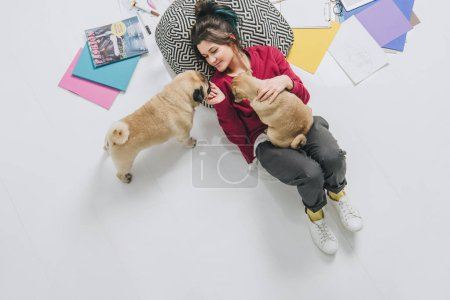 Young woman cuddling pugs on floor among sketches
