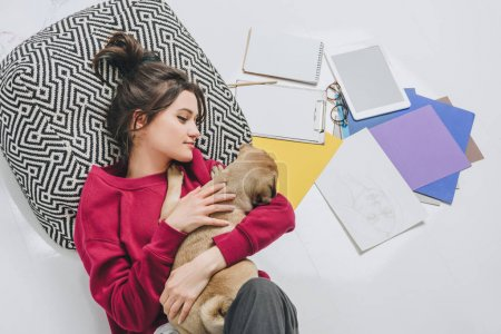 Pretty lady hugging cute dog on floor among sketches