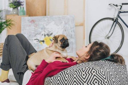 Photo pour Jeune femme jouant avec chiot Carlin sur sol de chambre moderne - image libre de droit