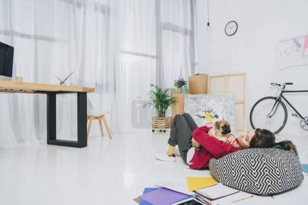 Pretty lady lying with pug on floor of modern home office