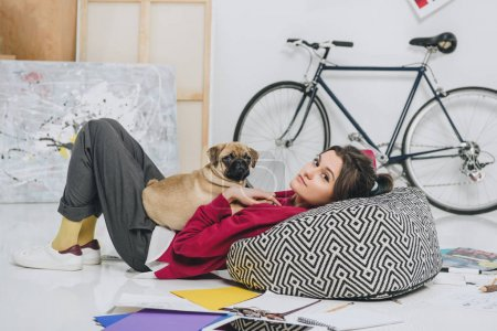Young woman lying on floor with pug