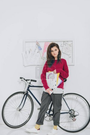 Young woman holding sketches and standing by bicycle
