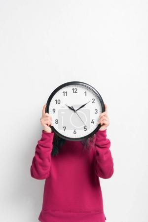 Girl holding clock over her face isolated on white