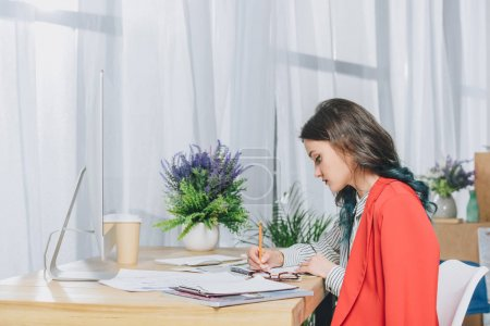 Pretty lady making notes by working table with computer
