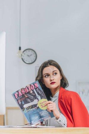 Pretty lady reading fashion magazine