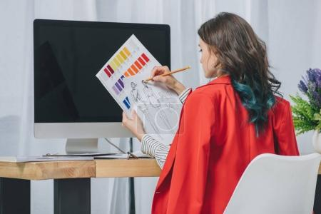 Young woman working with sketches by working table with computer