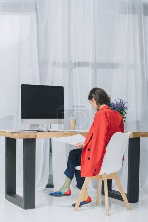 Attractive young girl working with sketches by table with computer