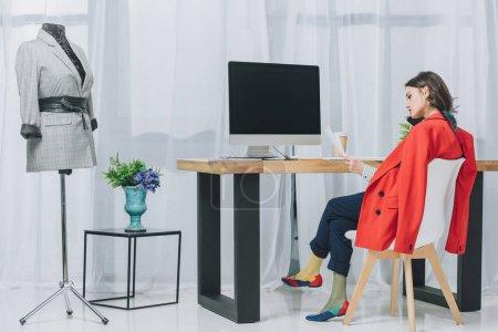 Muchacha joven atractiva hablando por teléfono mediante la mesa de trabajo con el ordenador