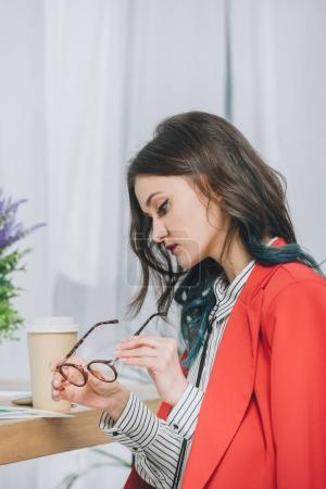 Young woman cleaning her glasses by working table