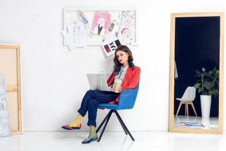 Pretty lady working on laptop and holding coffee cup in light studio