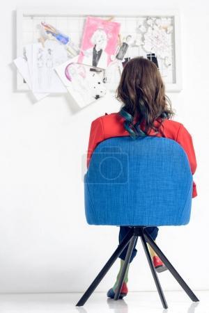 Rear view of woman looking at mood board
