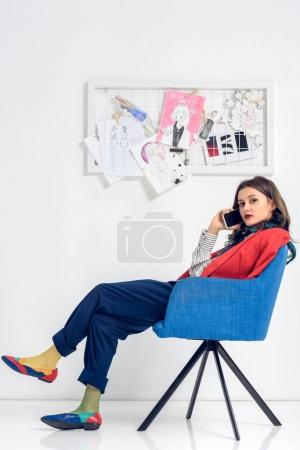 Young woman talking on the phone while sitting in chair