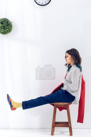Attractive young girl sitting on chair under clock