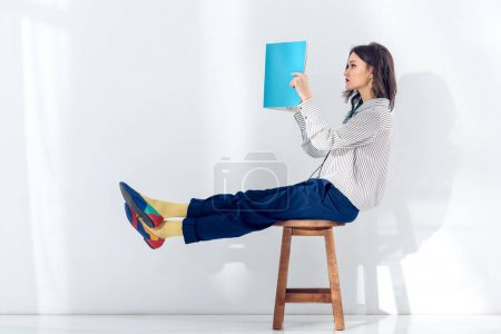 Young woman sitting on chair and reading book