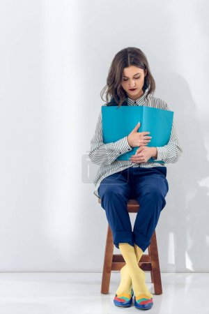 Photo for Young woman sitting on chair and reading book - Royalty Free Image