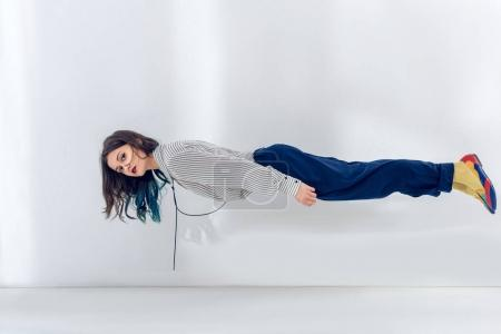 Pretty lady levitating on white wall background