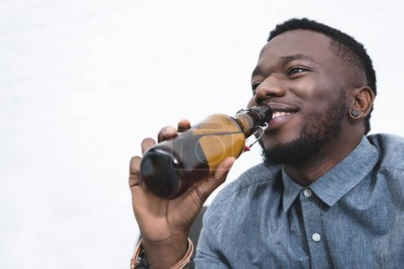 Handsome african american man drinking beer from bottle