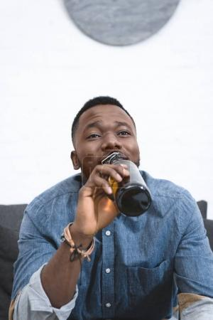 Young african american man drinking beer from bottle