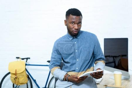 Young man using digital tablet and looking at camera