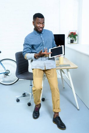 Photo for Young man showing on digital tablet screen standing in home office - Royalty Free Image