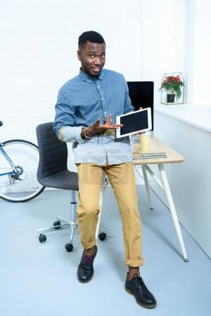 Young man showing on digital tablet screen standing in home office