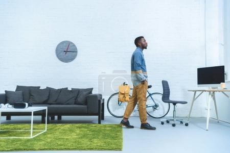 Handsome african american man standing in modern room with modern devices