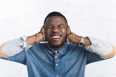 Photo pour Jeune homme riant et couvrant les oreilles - image libre de droit