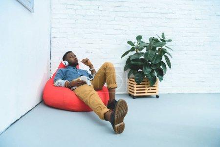 African american man listening to music in earphones while sitting in bean bag