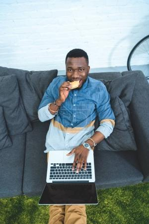 Handsome african american man working on laptop while sitting on sofa and eating hamburger