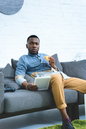 African american man holding tablet and eating hamburger