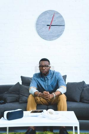 Modern gadgets on table in front of african american man sitting on sofa