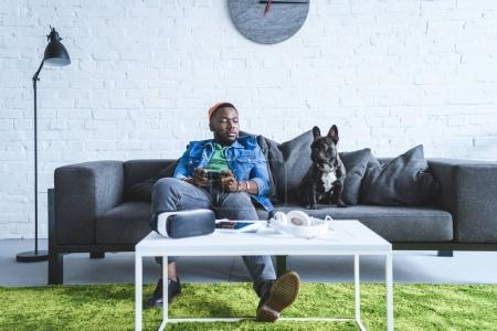 Photo pour Appareils numériques sur la table devant un jeune homme tenant un joystick et un canapé assis par un bouledogue français - image libre de droit