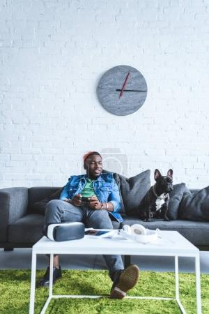 Young man holding joystick while sitting on sofa with bulldog and digital gadgets on table