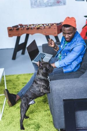French bulldog by African american man sitting on sofa with laptop