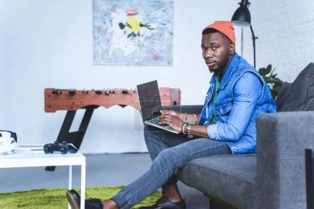 Handsome african american man working on laptop while sitting on sofa