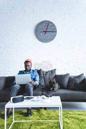 Digital devices on table in front of young man working on laptop and sitting om sofa by French bulldog
