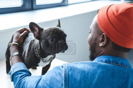African american man cuddling cute French bulldog