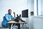 French bulldog lying on table with computer by handsome african american man