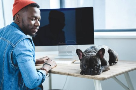 Bored dog waiting for African american man to finish work by computer