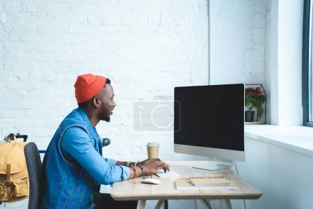 African american man typing on keyboard by working table