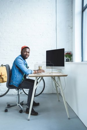 African american man working by table with computer