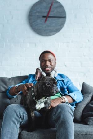 Handsome african american man in headphones cuddling French bulldog