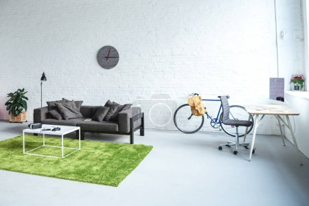 Digital gadgets in modern interior with grey sofa and workplace
