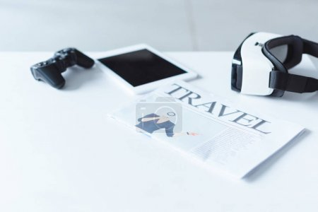 Digital gadgets and Travel newspaper on table