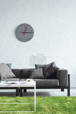 Cozy interior with modern grey sofa and clock on wall