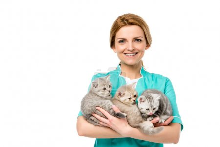 beautiful young veterinarian holding adorable kittens and smiling at camera isolated on white