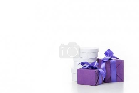 close up view of arrangement of various wrapped white and purple gifts isolated on white